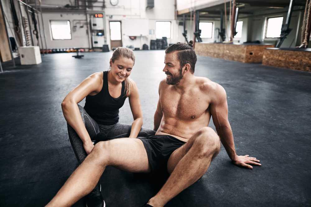 Dwie osoby odpoczywają na podłodze siłowni po ćwiczeniach